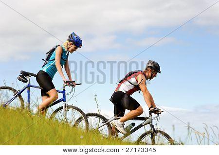 Pareja feliz andar en bicicleta afuera, concepto de la diversión de estilo de vida saludable