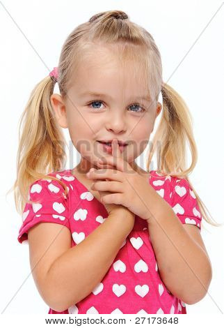 young girl with finger on lips gestures to be quiet