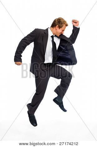 Attractive blond man celebrates by jumping raises his fist overhead
