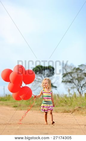 Young caucasian girl walks with a bunch of helium filled red balloons