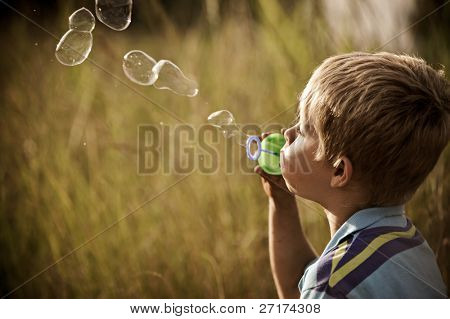 Young blonde boy blows a long string of bubbles in a field; image graded in a vintage tone