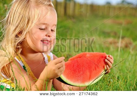 Cute blonde girl eats a watermelon whilst sitting in the grass