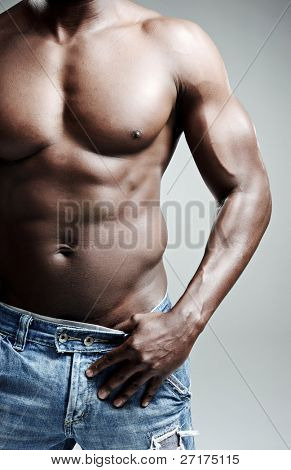 Shirtless muscular body in studio, on grey background