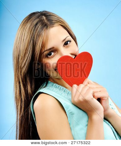 Beautiful young woman hides behind a red heart shy to profess her love
