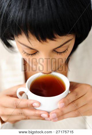 Attraktive Brünette genießt ihre Tasse Tee, bevor sie zur Arbeit geht