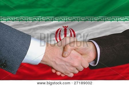 Businessmen Handshake After Good Deal In Front Of Iran Flag