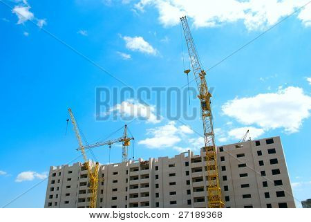 Building crane and building under construction on blue cloudy sky