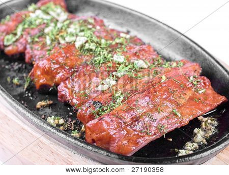 Spare ribs and greens closeup for dinner at pan isolated on a white