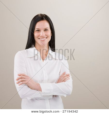 Studio shot of confident woman standing with arms crossed