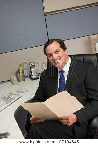 Smiling businessman holding file folder at desk in cubicle