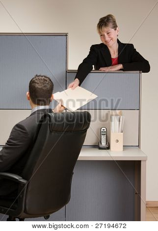 Businesswoman handing co-worker file folder at desk in cubicle