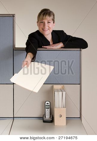 Happy businesswoman offering file folder over cubicle wall