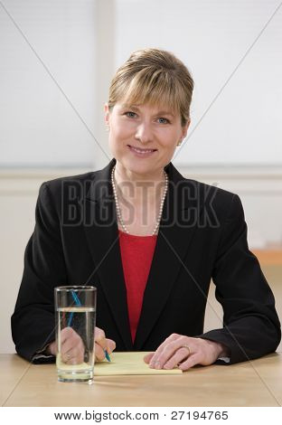 Smiling businesswoman writing on legal pad taking notes