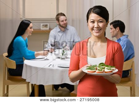 Mujer sosteniendo el aperitivo y servir a amigos en elegante cena