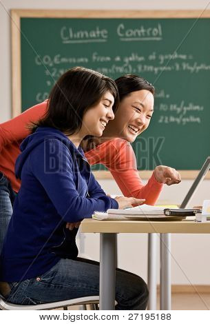 Determined student with laptop doing homework with friend in school classroom