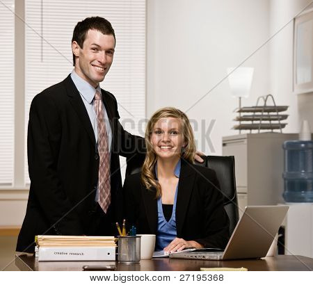 Happy, confident co-workers posing at desk