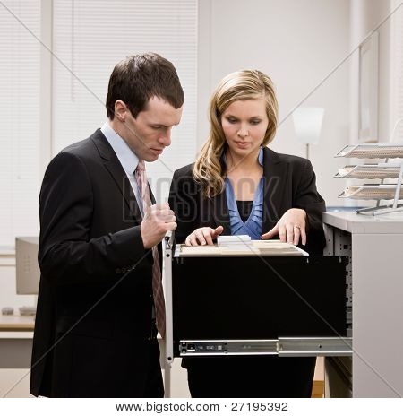 Co-workers searching through file drawers for folder