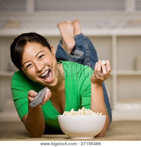 Happy woman laying on floor with bowl of popcorn, remote control and watching television