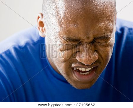 Fatigued man dripping sweat and grimacing