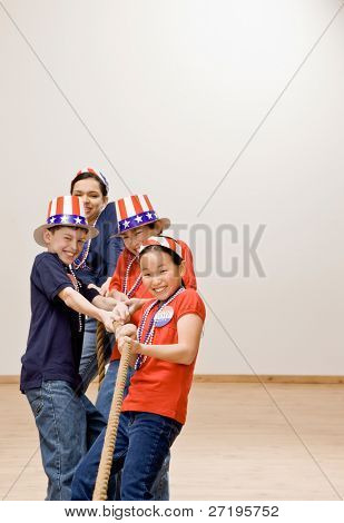Determined, patriotic children wearing American flag hats and pulling rope in tug-of-war