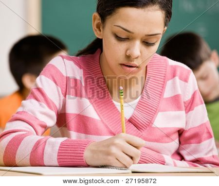Concentrating student writing in notebook in school classroom