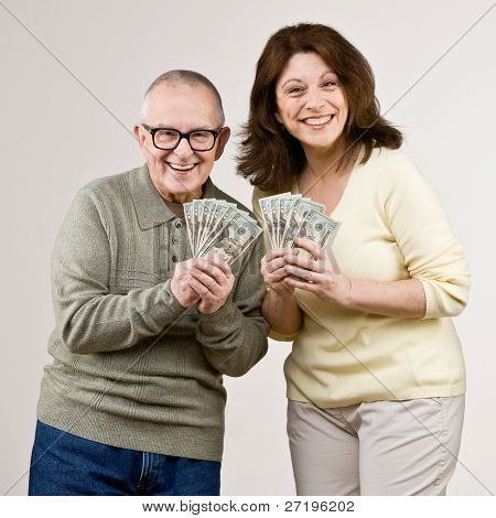Lucky, wealthy friends excitedly holding group of twenty dollar bills