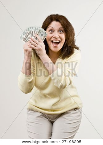 Lucky, wealthy woman excitedly holding group of twenty dollar bills