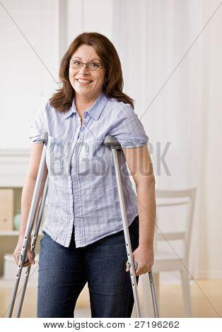 Mujer con discapacidad agraviada usar muletas para caminar