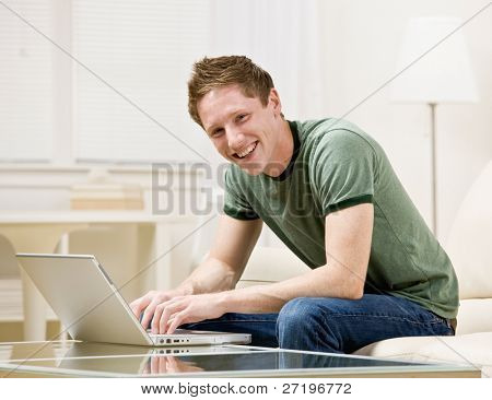 Man sitting on sofa in livingroom typing on laptop