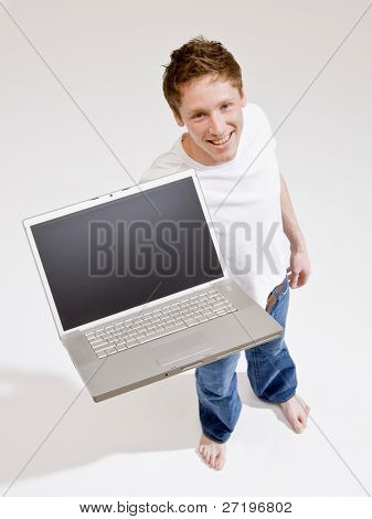 Confident barefoot man holding laptop