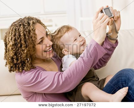 Devoted mother taking self-portrait of herself and happy son with digital camera
