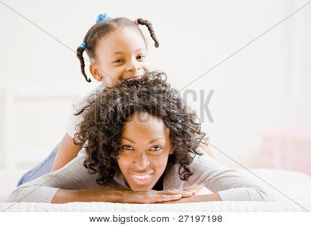 Devota de la madre pone en cama con hija juguetón