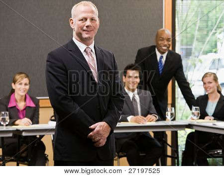 Confident businessman standing in front of co-workers in conference room