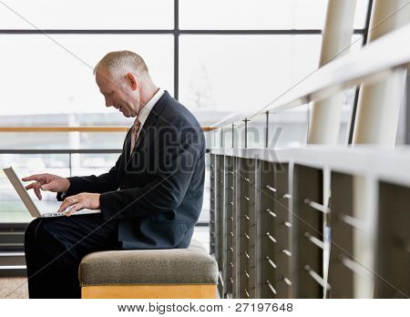 Side view of mature businessman working on laptop in office lobby