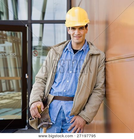 Male construction worker posing in hard-hat and tool belt