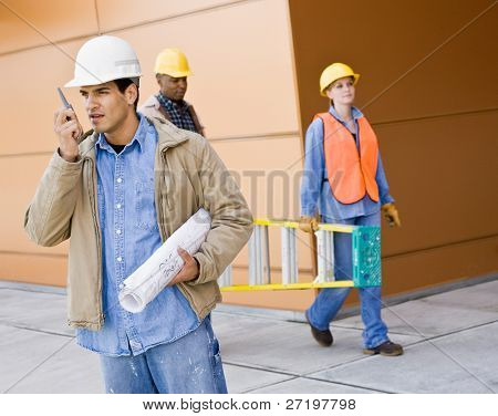 Busy construction workers carrying ladder, blueprints and talking on cell phone