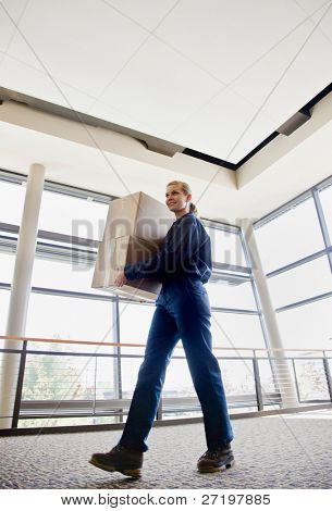 Low angle view of delivery woman in uniform carrying cardboard box