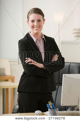 Confident businesswoman with arms crossed at desk