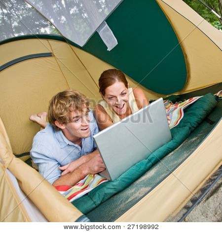 Couple laying in tent using laptop