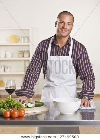 Attractive male chef in the kitchen with vegetables and a glass of wine on the counter. Vertical