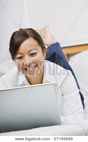 Attractive Asian woman lying down and smiling while working on a laptop. Vertically framed photo.