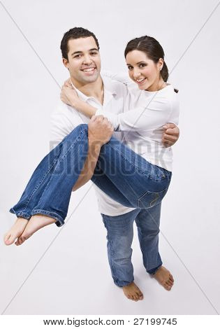 An attractive young man holding a beautiful woman in his arms.  They are smiling at the camera.  Vertically framed shot.