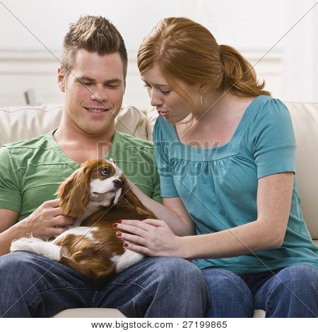 A young and attractive couple holding and petting a dog. Square framed photo.