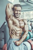 Brutal Aged Strong Bodybuilder Athletic Men Pumping Up Muscles With Dumbbells poster
