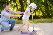 Middle Age Father Showing His Toddler Son How To Ride A Scooter In Summer Park. Active Family Leisur poster