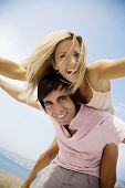 stock photo of summer fun  - young couple fooling around on the beach - JPG