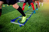 Young Boy Soccer Players Jogging And Jump Between Ladder Drills For Football Training. poster