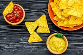 Snack For Party. Mexican Nachos Near Salsa And Guacamole Sause On Black Background Top View Copy Spa poster