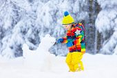 Child Making Snowman. Kids Play In Snow In Winter poster