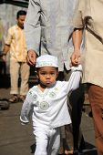 JAKARTA, INDONESIA - SEPTEMBER 20: Parents take their young child to the mosque for prayer on Hari R